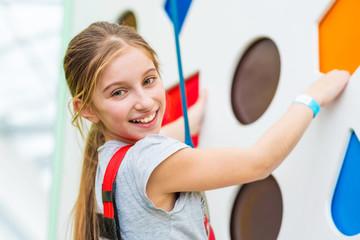 Cute little kid girl in sport equipment climbing