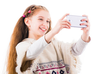 Smilling young little girl makes selfie with her mobile phone isolated on white background