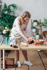 Photo of florist woman making bouquet of marshmallows, flowers