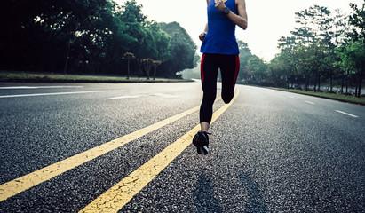 Fitness sportswoman running on sunrise trail