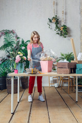 Photo of beautiful florist decorating floral composition at table with flowers, boxes
