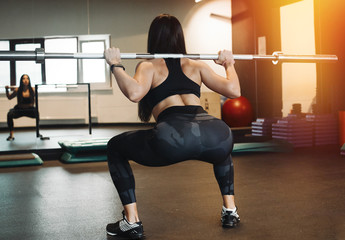 Young attractive brunette girl sit ups with barbell. Female successfully practices workout and crossfit training. Blurred background and focus on young woman back and up view. Female practicing sit up