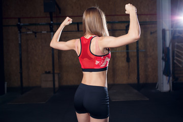 Photo from back of sports woman showing biceps