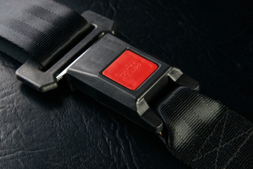 Fastened seat belt on black leather background, close-up. Safety concept