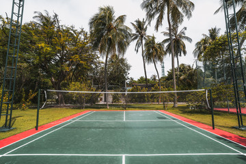Wide-angle frontal view of a cozy badminton court on a summer day: red and green field with marking on the ground, multiple palm trees, lighting masts on sides