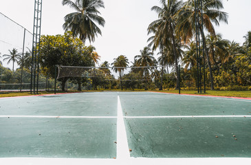 Wide-angle view from the bottom of badminton court on a summer day: green and red field with marking on the ground, multiple palm trees, lighting masts on sides, stripes following to a vanishing point
