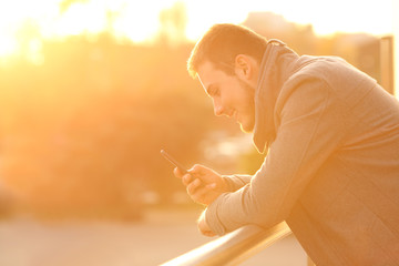 Happy man using a smartphone in winter at sunset