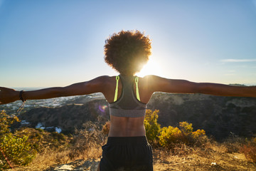 athletic african american woman celebrating reaching top of runyon canyon with arms open