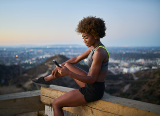 athletic african american woman using smartphone at runyon canyon while resting on bench at dusk