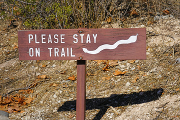 Sign warning hikers to stay on trail because of snakes at the Montezuma Castle National Monument cliff dwellings in Camp Verde, Arizona