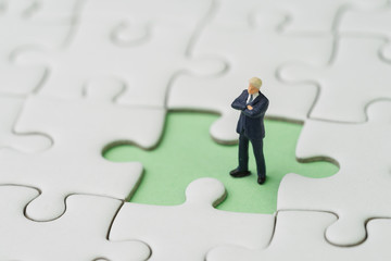 Missing key person for business success strategy concept, miniature people businessman standing  at the missing white jigsaw puzzle piece on pastel green background