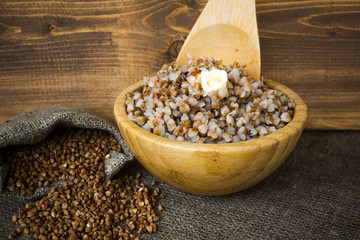 Boiled buckwheat groats in bowl with butter, a baggie of dry cereal. Wooden background.