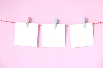 Blank white papers notepad hanging on pink background