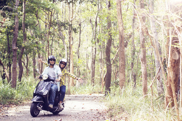 Beautiful young couple in helmets riding a scooter through forest. life style idea concept