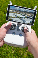 Hands Holding Drone Quadcopter Controller With Indutrial Buildings on Screen