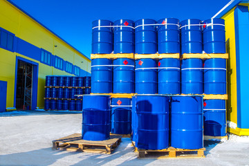 Chemical reagents. The blue barrels stand on pallets. Chemical industry. A wall of barrels.