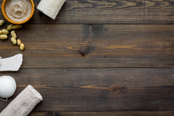 Homemade spa with organic scrub and peanut on wooden background top view space for text