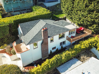 Aerial view of a large white home with spacious deck.