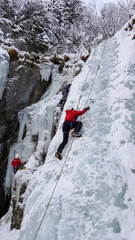 ice climbers on a n ice fall in the Swiss Alps during an ice climbing course