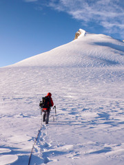 male mountain climber heads towards a high alpine summit over a glacier with fresh snow