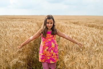 Happy little girl in a field of ripe wheat