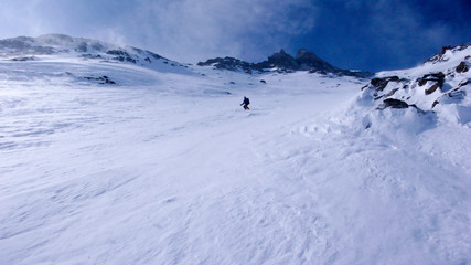 extreme skier in the back country on a very steep north face descent in the Alps in high winter