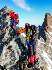 male and female mountain climber on an exposed rocky summit ridge on their way to a high alpine mountain peak