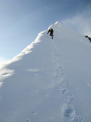 male mountain climber on his way to a high summit in the Alps after exiting a hard north face climbing route