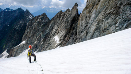 male mountain climber takes a break on a high alpine glacier and looks at his way down and the descent route