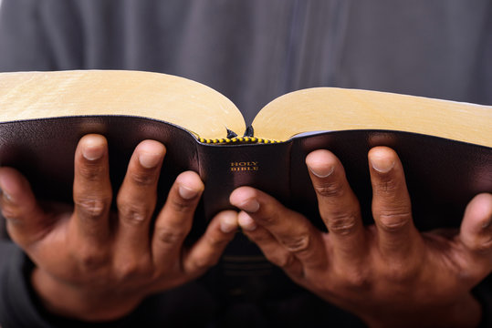 A close up view of a man hands holding the Holy Bible
