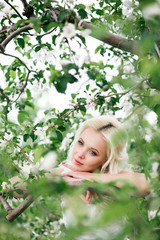 Amazing blonde bride in blooming apple garden