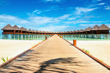 Wooden bridge leading to an exotic bungalow on the background of azure water, maldives