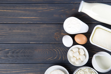 Dairy products on wooden table. Milk, cheese, egg, curd cheese and butter.