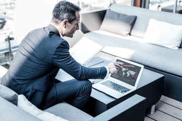 World trade. Positive cheerful smart businessman sitting in front of the laptop screen and looking at the map while working