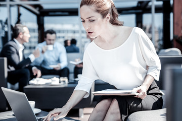 Business papers. Nice serious pleasant businesswoman sitting in front of the laptop and pressing a button on it while holding documents