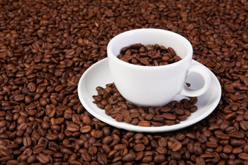 white cup of coffee at coffee beans backgrounds