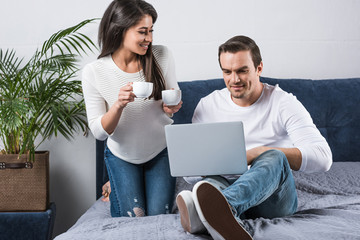 smiling african american woman holding cups of coffee and looking at boyfriend using laptop on bed