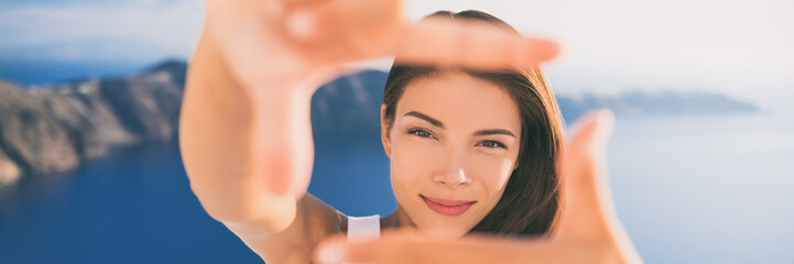 Wall Mural - Beautiful young woman framing face with hands portrait banner panorama. Asian beauty Chinese Caucasian model in summer background. Europe travel vacation, luxury Santorini Greece holiday.