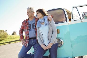 Cheerful senior couple standing in front of camper van