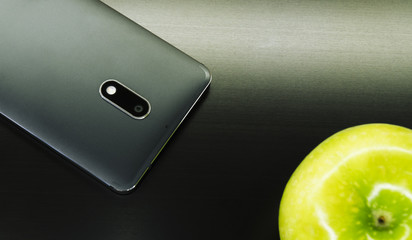black phone with a green apple on a black computer