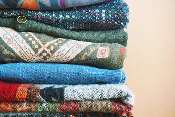 Stack of warm clothes of different patterned fabrics in boho style.