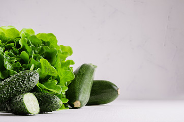 Deep green different vegetables on soft white wood table with copy space. Healthy summer raw food.