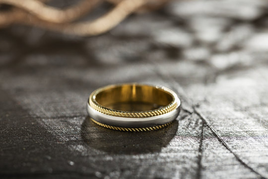 Silver and gold ring on black background