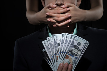 Woman closes mouth a man in suit holds money. Bribe and Corruption. Don't speak
