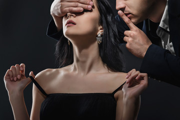 Man covers eyes and shows silence gesture to gorgeous woman on black background