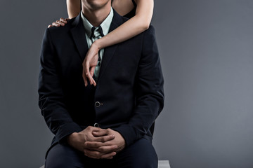 Elegant man in suit sits and beautiful woman embraces him on grey background