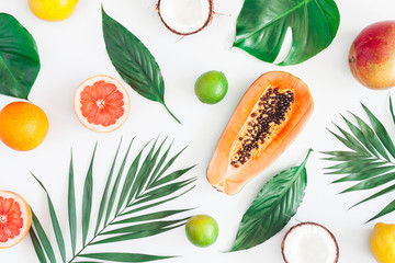 Summer tropical composition. Green palm leaves and tropical fruits on gray background. Summer concept. Flat lay, top view