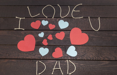 forming the word: i love DAD on wooden background