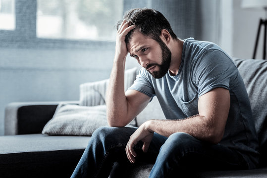 Unpleasant pain. Sad unhappy handsome man sitting on the sofa and holding his forehead while having headache