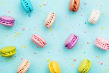 Türaufkleber Desserts Colorful cake macaron or macaroon on turquoise pastel background from above. French almond cookies on dessert top view.